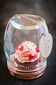A red velvet cupcake with vanilla frosting and sugar hearts for Valentine's Day