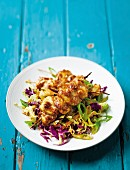 Spicy chicken kebabs on a bed of cabbage salad