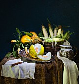 An autumnal arrangement with melons, pumpkins and sweetcorn