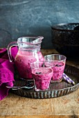 Blueberry smoothie in a jug and glasses