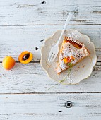A slice of apricot pie on a plate with a fork