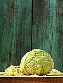 A whole and chopped savoy cabbage on a wooden board
