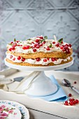 A cake with white chocolate cream and redcurrants on a cake stand