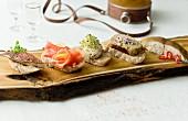 Verschiedene Crostini mit Räucherforelle, Räucherlachs, Makrelenpate, Aalpate und geräuchertem Heilbutt