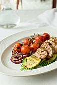 Grilled pork tenderloin with grilled tomatoes, zucchini and red onion