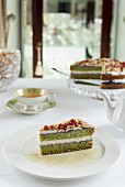 Spinach and pistachio sponge cake with pomegranate seeds and berry mousse