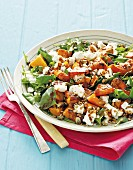A miexd salad with roasted butternut squash, rocket, feta cheese and grains