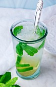 A Mojito cocktail with lime and mint in a chilled glass