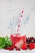 A bottle of strawberry & redcurrant milkshake with fresh berries and mint