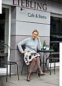 Blonde Frau in grauem Strickpullover, Rock mit Blumenprint und Stiefeletten sitzt im Straßencafé