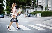 Blonde Frau in rosafarbenem Cashmere-Mantel, Plisseerock, Pumps und Henkeltasche
