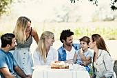 Familie und Freunde an einem Gartentisch