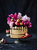 A naked cake with macarons and flowers
