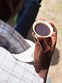 A man holding a cup of Ethiopian coffee at a traditional Ethiopian coffee ceremony