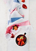 Fresh strawberries in a cup and on a tea towel