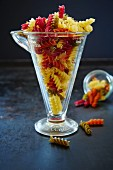 Colourful fusilli pasta in a measuring cup and a glass