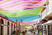 A lane decorated with colourful cloths in the old city centre of Loulé in the Algarve region of Portugal