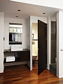 Elegantes Badezimmer mit Edelholzparkett und Aufsatzbecken, offene Tür zur abgetrennten Toilette