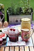 A breakfast table in the garden with jam, charcuterie and eggs