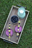 Blueberry smoothies on a wooden tray in the garden