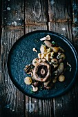 Assorted mushrooms with onions and herbs on a metal plate