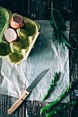 Grüner Spargel, Eierschalen im Eierkarton und frischer Estragon