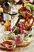 Brettljause (Bavarian ploughman's lunch) with pretzels, dips, vegetables and red wine