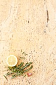 A stone background with lemon, garlic, rosemary and thyme