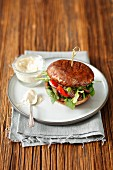 A portobello mushroom burger with grilled beef, pickled pepper and cucumber