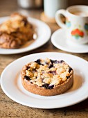 Berry crumble tartlet with a cup of coffee in a French café