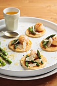 Blinis with scallops, asparagus and orange sauce