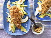 Chicken with a sesame seed coating on a bed of pear & avocado salad