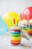 Mini Regenbogen-Schichtkuchen mit Geburtstagskerzen in einem Glas