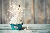 Weihnachts-Cupcake mit Wunderkerze verziert