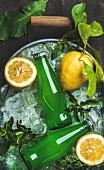 Limonade in Flaschen und Zitronen auf Crushed Ice in einem Metallbehälter