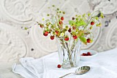 Glass vase of wild strawberries with flowers and fruit