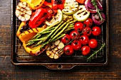 Grilled vegetables on metal grid baking sheet on wooden background