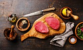 Raw tuna steaks fillet with lemon and sesame on olivewood cutting board