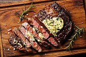 Sliced grilled Medium rare barbecue steak Ribeye with herb butter on cutting board