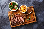 Sliced grilled Medium rare barbecue Steak on bone Veal rib with potato wedges and tomato and arugula salad