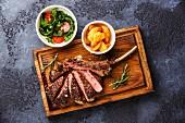 Gegrilltes Kalbskotelett, medium, Potato Wedges und Rucola-Tomaten-Salat auf Holzbrett