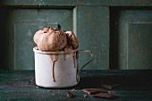 Frozen vintage aluminum mug with melting chocolate ice cream balls, served with chopped dark chocolate