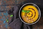 Black ceramic bowl of pumpkin and sweet potato cream soup with fresh basil, fried onion and balsamic sauce