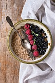 Bowl of oatmeal porridge with blueberries, raspberries and chia seeds