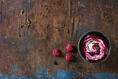 Black ceramic bowl of raspberry dessert soup with cream