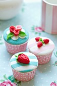Cupcakes decorated with fondant strawberries and roses in pink polka dot cupcake cupcake cups