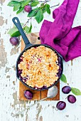 Plum crumble in a frying pan with oats and flaked almonds