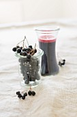 Fresh aronia berries and home-made aronia berry juice in glasses