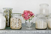 Storage jars (old preserving jars) with muesli, rice, verbena leaves and flour on a zinc shelf in the kitchen
