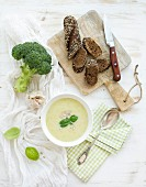 Homemade broccoli cream soup in white bowl with fresh rye baguette on wooden board